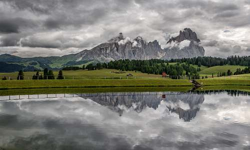 italy landscape photo of body of water near the field mountains