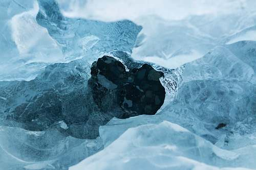 photo snow A hole in an ice sheet covering dark blue water ice free for commercial use images