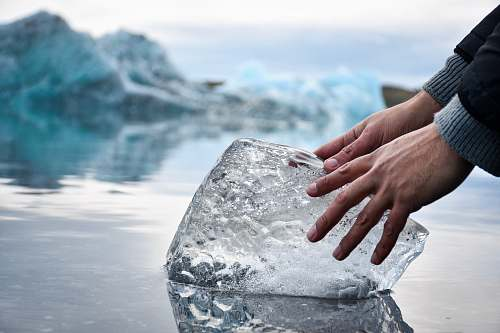 photo ice person with hands on ice block on water during daytime outdoors free for commercial use images