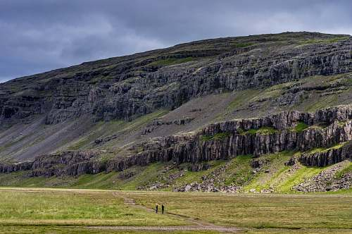 photo field two people standing on field near cliff landscape free for commercial use images