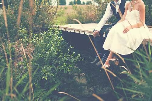 human couple sitting on wooden bridge wedding
