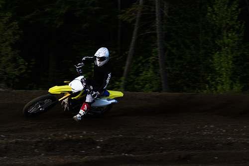 human man ridding yellow and white motocross dirt bike back