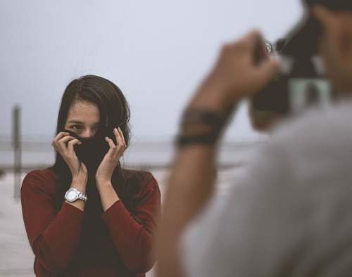 human selective focus photography of person wearing white shirt taking photo of woman wearing red long-sleeved shirt covering her face with hair person