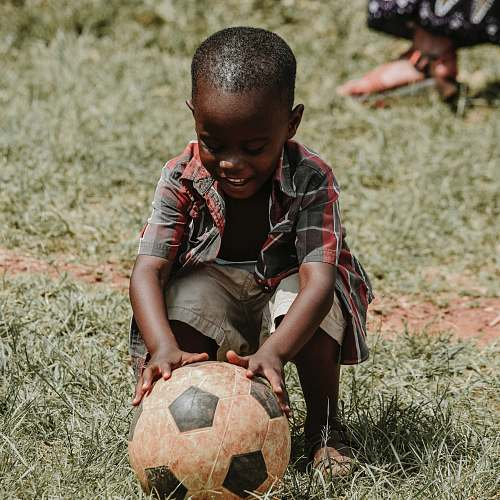 football smiling boy sitting while holding soccer ball at daytime soccer