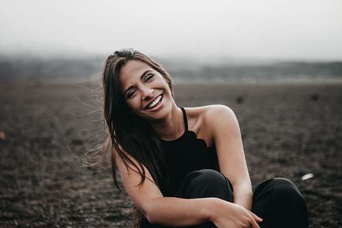 photo person woman laughing while sitting on ground woman free for commercial use images