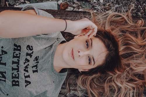 girl woman wearing gray t-shirt lying on ground portrait