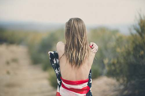 human focus photography of half naked woman covering body with USA flag woman