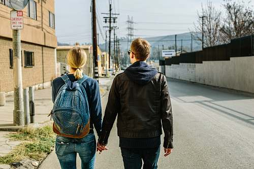 couple man holding hands of woman walks on concrete road back