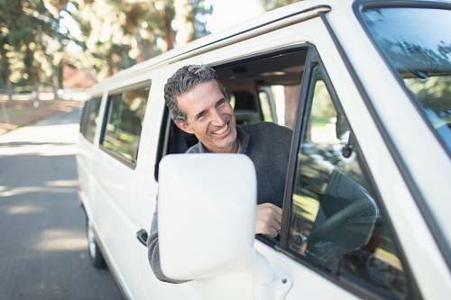 smile man in gray sweater leaning on van window car