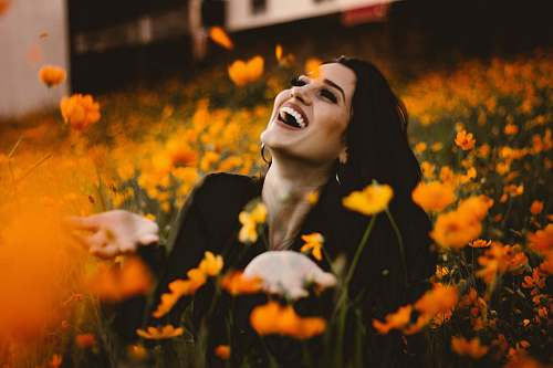 human woman laughing on flower field face
