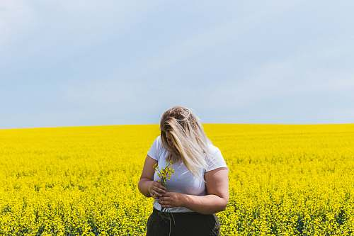 field woman standing and holding flowers on flower field girl