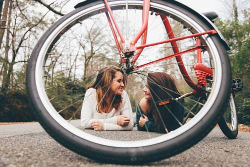 photo people woman wearing white scoop-neck long-sleeved shirt besides woman wearing green off-shoulder shirt on the floor bicycle free for commercial use images