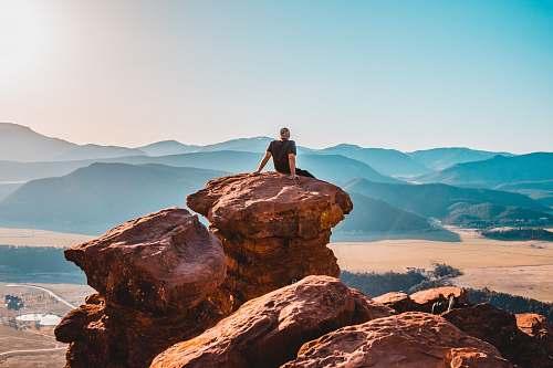 sitting man sitting on rock formation mountains