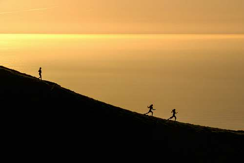 sunrise three persons running downhill during golden hour sunset