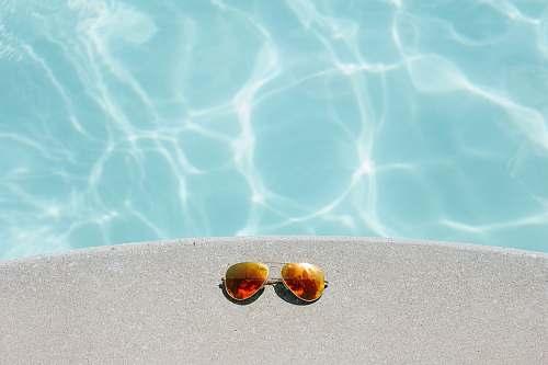 summer gold framed orange lens Aviator-style sunglasses beside pool glasses