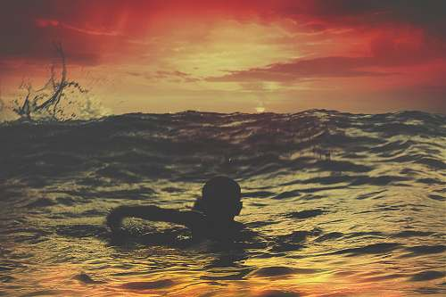 photo sunset person swimming on body of water under red and orange sky sunrise free for commercial use images