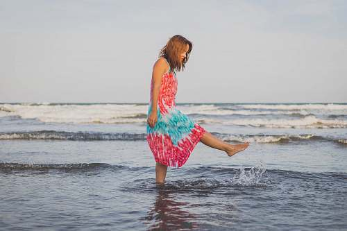 beach woman playing with water on shore during daytime coast