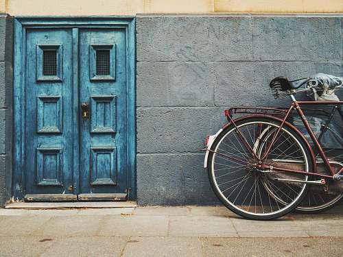 door minimalist photography of parked bicycle near blue door bike