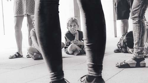 person grayscale photography of boy sitting on the floor watching the person in front of him people