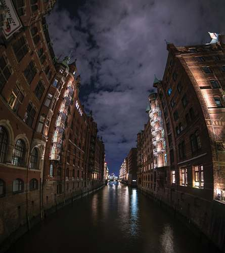 water brown and black concrete building during nighttme speicherstadt