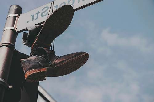 germany pair of black boots hanged on street post boot
