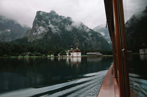 lake brown wooden boat on body of water in front of mountain photo fog