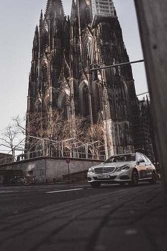 cologne gray car on asphalt road near castle during daytime church