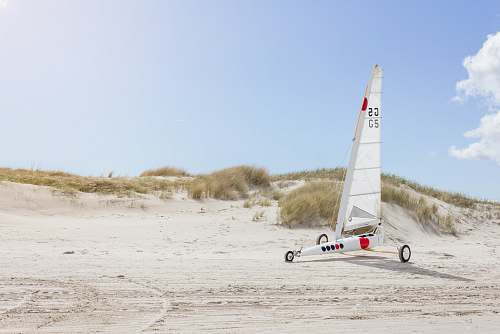 sea landscape photo of white sailboat with wheels on sand dunes