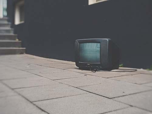 television turned off black CRT TV near black concrete wall tv