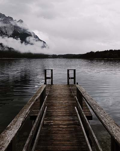 pier brown wooden dock near mountain at cloudy sky dock