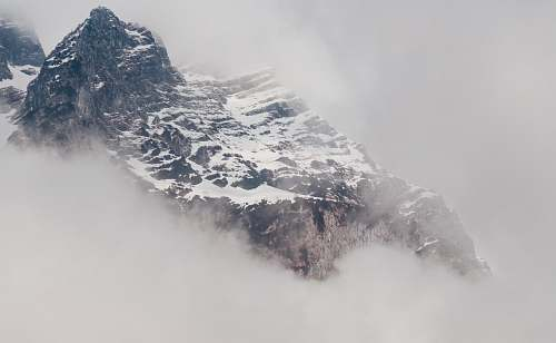 grey snowy mountain covered by fog mountain