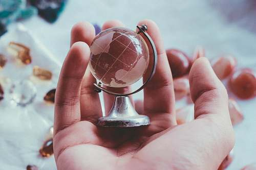 glass person holding gray metal framed desk globe paper weight prism