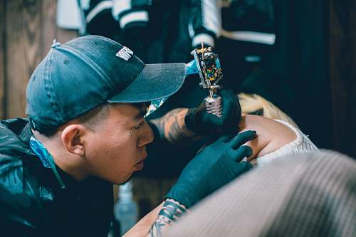 clothing man holding gray rotary tattoo machine making tattoo on person arm hat