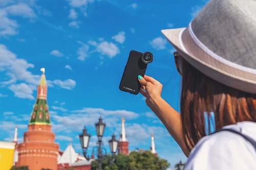 clothing woman taking self portrait with clip-on zoom lens in smartphone hat