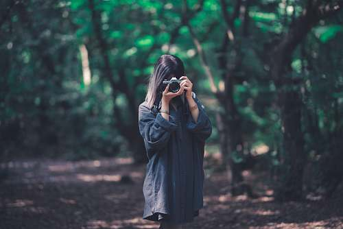 photo clothing woman using camera near trees coat free for commercial use images
