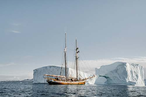 transportation brown boat near ice berg during daytime vehicle