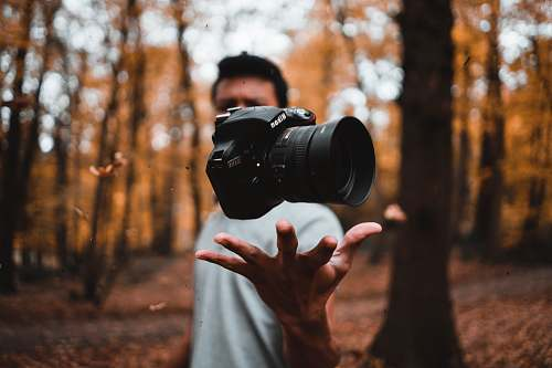 person black DSLR camera floating over man's hand at the woods electronics