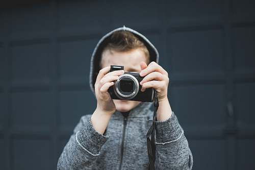 photo human person in grey hoodie holding up camera over face person free for commercial use images