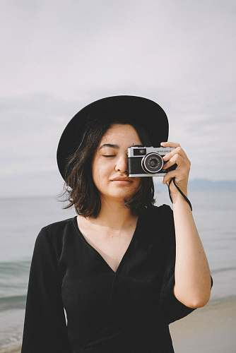 human woman holds camera near to her right eye at the beach person