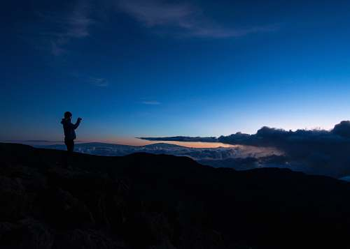 cloud silhouette of man taking photo on rock cliff mountain