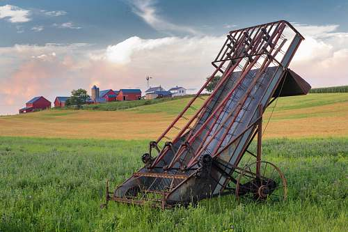 farm grey and red metal harvester machine on green field barn