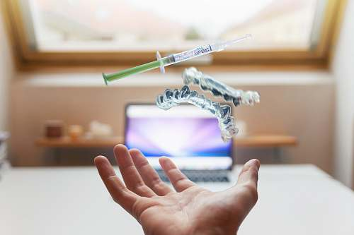 dentist open palm with syringe floating above hand