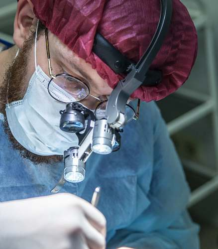 surgeon man wearing head microscope clinic