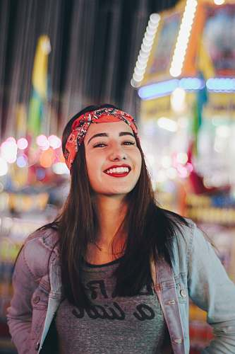 smile selective focus photography of smiling woman wearing red and black bandana human