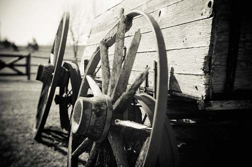 wheels grayscale photo of wagon wheel person