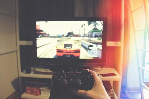 photo apartment person holding Sony PS3 controller in front of flat screen monitor tv free for commercial use images