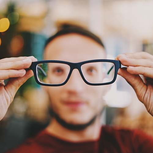 human person holding eyeglasses with black frames person