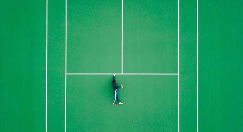 tennis aerial photography of person lying on tennis court sport