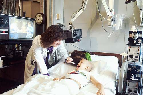 display A doctor examines a pediatric patient who is receiving chemotherapy. electronics