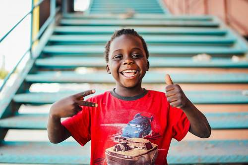 photo people boy standing near stairs doing peace sign at daytime person free for commercial use images